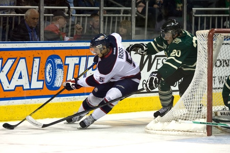 London Ontario, Canada - April 13, 2012. Garret Ross (5) of the Saginaw Spirit stretches to avoid a check from Kevin Raine (20) of the London Knights. The London Knights defeated the Saginaw Spirit 2 - 1 in overtime at the John Labatt Centre taking a thre Stock Photo - 13154720