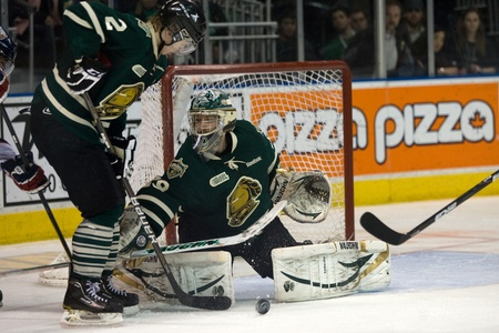 john labatt centre: London Ontario, Canada - April 13, 2012. London Knight goalie Michael Houser makes a save while defenceman Ollie Maatta (2) prepares to clear the puck. The London Knights defeated the Saginaw Spirit 2 - 1 in overtime at the John Labatt Centre taking a thr