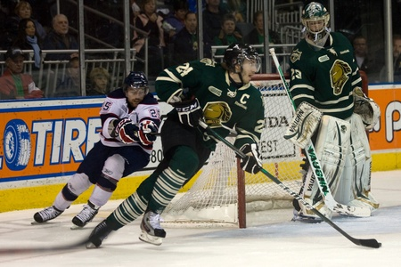 London Ontario, Canada - April 13, 2012. Jarred Tinordi (24) of the London Knights avoids a check from Josh Shalla (25) of the Saginaw Spirit and starts to carry the puck up the ice. The London Knights defeated the Saginaw Spirit 2 - 1 in overtime at the  Editorial