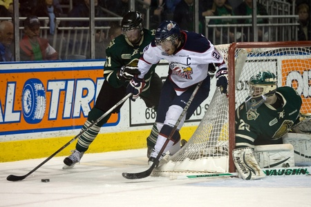 London Ontario, Canada - April 13, 2012. Brandon Saad (22) of the Saginaw Spirit battles to control the puck while Austin Watson (51) of the London Knights tries to prevent the play. The London Knights defeated the Saginaw Spirit 2 - 1 in overtime at the  Stock Photo - 13154721