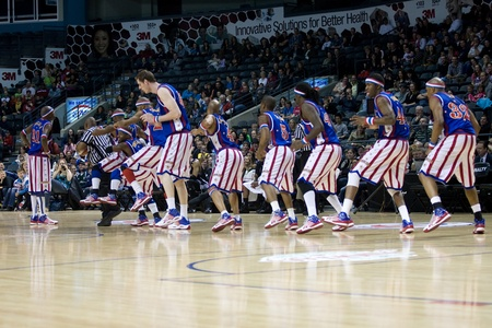 London Ontario, Canada - April 14, 2012. Members of the Harlem Globetrotters lline up behind the referee and mimic the same moves. The Harlem Globetrotters brought their show and defeated the International Elite to win the World Championship at the John