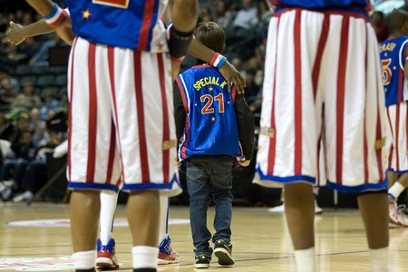 London Ontario, Canada - April 14, 2012. A young fan leaves the court wearing a team jersey after making a basket. The Harlem Globetrotters brought their show and defeated the International Elite to win the World Championship at the John Labatt Centre i Editorial