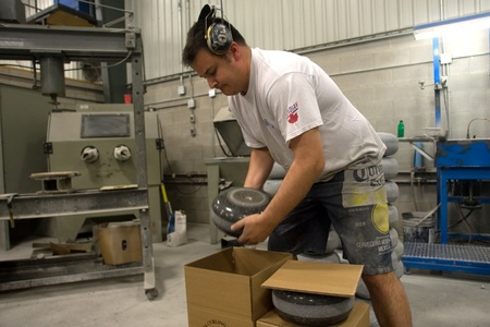April 26, 2012. Wayne Tuck of Canada Curling Stone packs a refurbished curling stone into a box for shipping. Canada Curling Stone in Komoko Ontario, near London is one of two companies in the world that refinish curling stones.  The company was founded i Stock Photo - 13455542