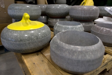 April 26, 2012. Curling rocks sit on a skid before going to be refinished. The rock with the yellow handle shows how it will look when completed, the one on the right is waiting for a new core to be installed. Canada Curling Stone in Komoko Ontario, near