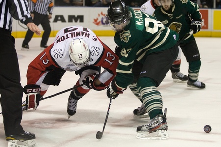 London Ontario, Canada - May 11, 2012. London Knights forward Greg McKegg (92) wins a faceoff over Freddie Hamilton (13) of the Niagara Icedogs. The London Knights defeated the Niagara Icedogs 2 -1 to win the Ontario Hockey League Championship series 4 -
