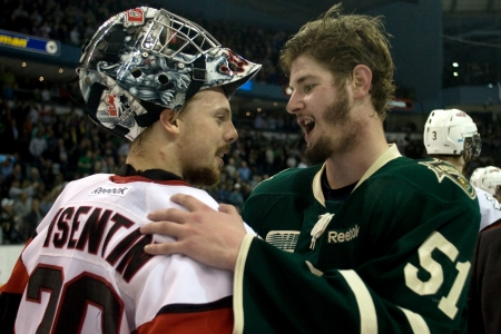 London Ontario, Canada - May 11, 2012. Ontario Hockey League Playoff MVP Austin Watson (51) of the London Knights congratulates Niagara Icedog goalie Mark Visentin after the game. The London Knights defeated the Niagara Icedogs 2 -1 to win the Ontario Hoc