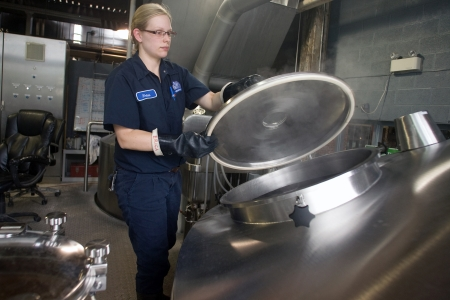 Toronto Ontario, Canada - June 5, 2012. Erica Graholm a brewer at Steam Whistle opens a Lauter Tun used to perform specific gravity test that measures fermentable sugars during the brew-in process. Located in a former Canadian Pacific Rail steam locomotiv Stock Photo - 14612391