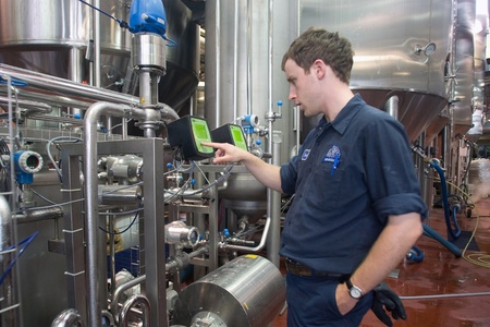 brewery: Toronto Ontario, Canada - June 5, 2012. Brock Edwards in the filtration department monitors the flow of beer through the filtration systems. Located in a former Canadian Pacific Rail steam locomotive roundhouse, Steam Whistle brewery produces an average o