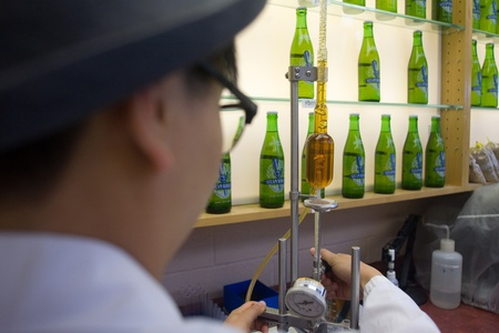 brewery: Toronto Ontario, Canada - June 5, 2012. Trish Yee, quality assurance technician tests a sample of beer for carbonation and head space gases. Located in a former Canadian Pacific Rail steam locomotive roundhouse, Steam Whistle brewery produces an average o
