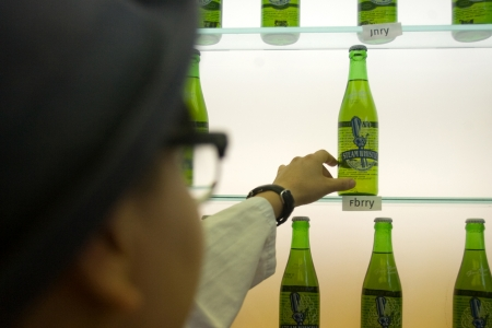 Toronto Ontario, Canada - June 5, 2012. Trish Yee, quality assurance technician inspects a bottle of beer for clarity. One bottle is pulled from the line on every production day and kept for several months where it is inspected on a regular basis. Located Редакционное
