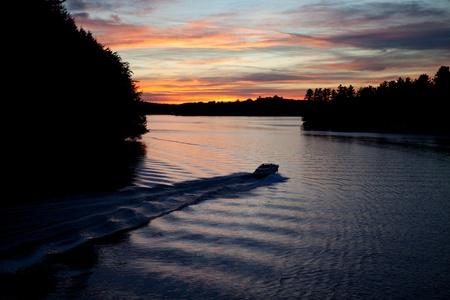 muskoka: Muskoka Ontario, Canada -  A pleasure boat heads out for a sunset crusie on Lake Rosseau in the Muskoka region of Ontario Canada.  Stock Photo