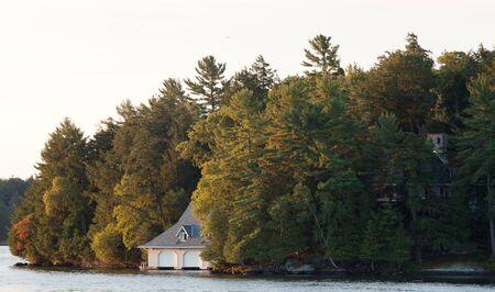 Muskoka Ontario, Canada -   Sunrise on Lake Rosseau in the Muskoka region of Ontario, illuminates a boat house and trees on one of the many islands located on the lake.   Редакционное