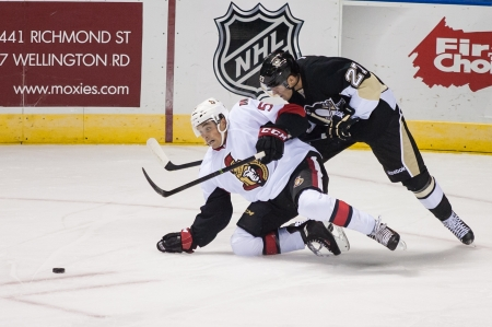Ottawa defenseman Cody Ceci (5) is checked to the ground by Pittsburg's Carter Rowney during a game at the 2013 National Hockey League Rookie Tournament being played at the Budweiser Gardens in London Ontario, Canada on September 5, 2013. The Ottawa Senat