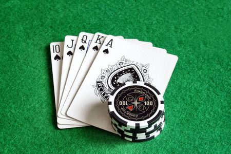 Poker chips with playing cards on green felt