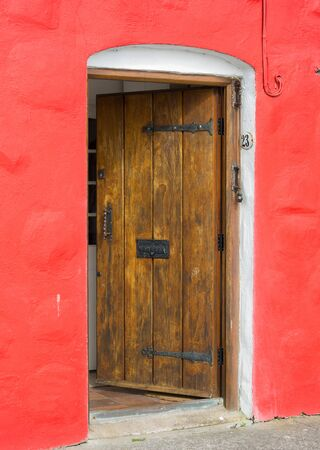 incorporated: Old wooden open door incorporated in the red wall. Street view taken in Galway, Ireland