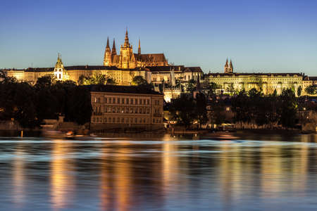 castle conditioning: Iluminated Prague castle. Evening light, Vltava river in the foreground.