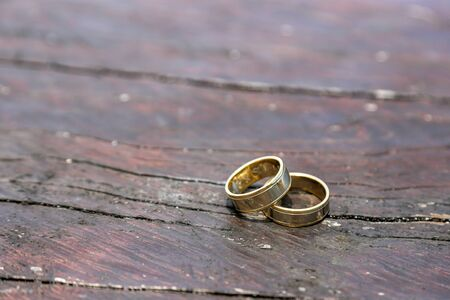 medium size: two medium size gold wedding rings placed on top of each other on the wooden brown table right corner.horizontal photo
