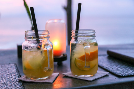 medium size: two medium size mojito jars with straws placed on a table with a small yellow lamp behind them and a person in the background