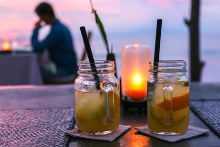 tropical drink: two medium size mojito jars with straws placed on a table with a small yellow lamp behind them and a person in the background