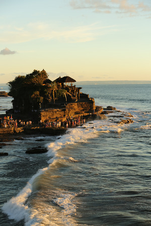 Rock formation with the Tanah Lot temple on top of it. Soft evening light and ocean waves hitting against the rock.  South of Bali, Indonesia. Vetical photo