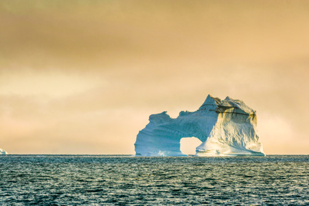 Rugged, powerful iceberg with an O floats off shore in the Arctic. Stock Photo