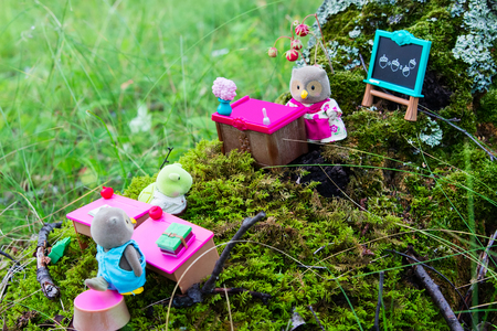 Sterlitamak, Russian Federation - Juli 10, 2016 Lil Woodzeez owl-mother, owl-son and turtle-son toy figures are in forest school. Owl-mother toy figure is teacher. Owl-son and turtle-son are pupils. Stock Photo