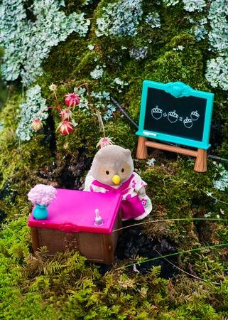 animal figurines: Sterlitamak, Russian Federation - Juli 10, 2016 Lil Woodzeez owl-mother toy figure teacher in school. Owl-mother toy figure stands near the teachers desk. Nearby is the school board and chalk.