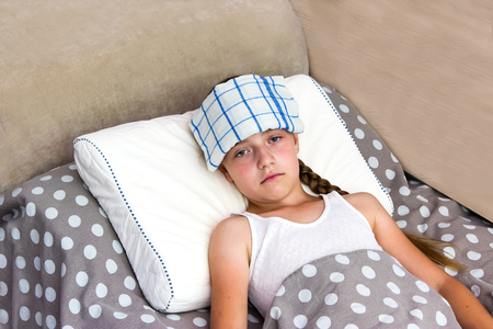 termometer: Girl with heatstroke on the bed with cool wet towel on her head.