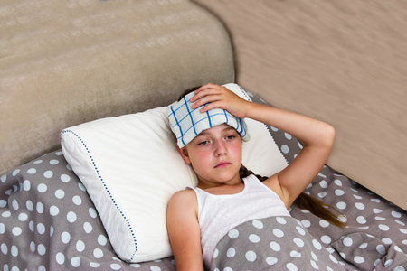 sunstroke: Girl with heatstroke on the bed with cool wet towel on her head.