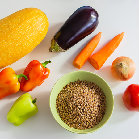 foodstuffs: Colored foodstuffs  - vegetables and speltal on a white table. Stock Photo