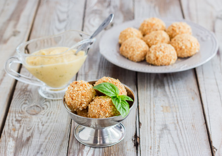 Cottage cheese balls in a peanut sprinkled with apple-basil sauce. Dessert masquerades as ice-cream. Stock Photo