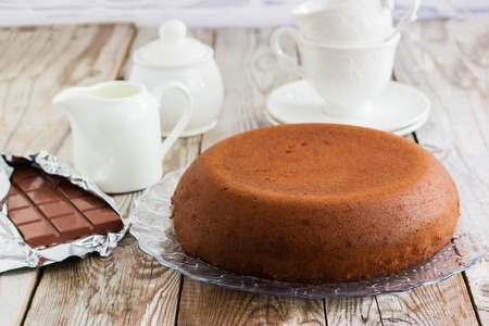 Chocolate-cottage cheese cake and white tea-set on wooden background.