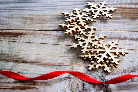 Snowflakes and red ribbon on wooden background. Winter holidays concept.