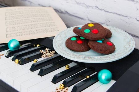Christmas cookies and music sheet on piano.