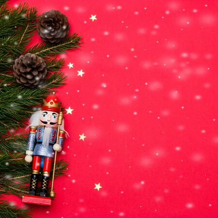Composition with nutcracker and golden stars on red background. Reklamní fotografie