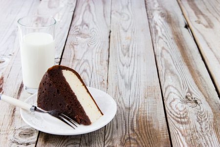 Two layered cake: chocolate and cottage cheese and milk on wooden background. Stock Photo