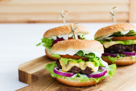 grill: Domestic burgers beef wooden cutting board cotton napkin. Stock Photo