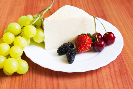 Wedge Adygea cheese summer berry healthy food wooden table. Stock Photo