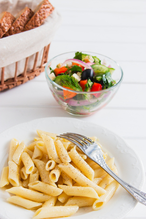Cooked penne with useful vegetables salad white table. Stock Photo