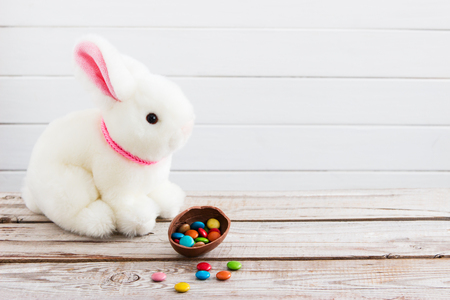 Easter background white bunny dragee chocolate egg. Banco de Imagens - 83733591