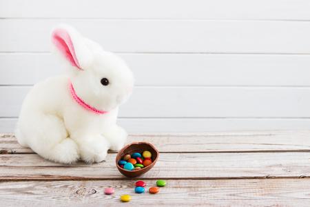 Pasen-achtergrond wit de chocoladeei van konijntjesdragee.