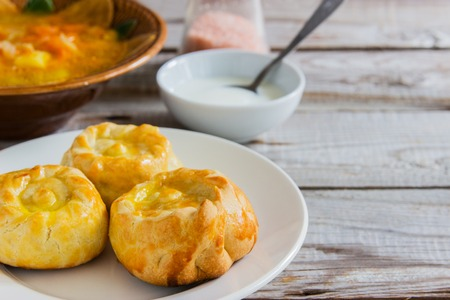 Russian traditional pies kurniki with cabbage soup on wooden background. Reklamní fotografie