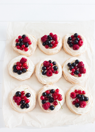 Six fresh mini berry pavlova kitchen wooden table selective focus.