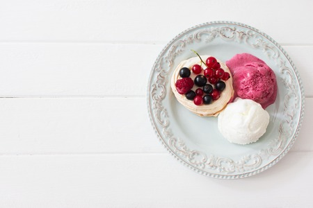 Three dessert ice cream berry pavlova nests kitchen wooden table selective focus.