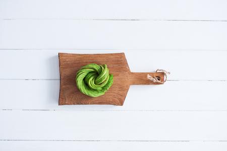 Raw vegan avocado rose wooden cutting board.