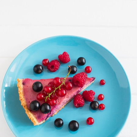 Wedge beautiful ripe currant tart top view blue plate square.