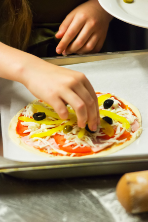Process pizza cooking dough little girl hands selective focus.