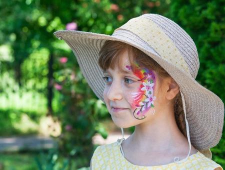 Little girl festive face art smiling summer day. Stock Photo