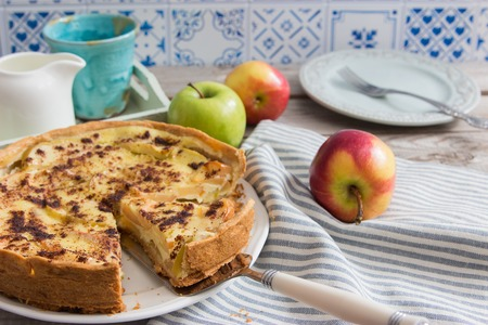 Apple tart cut pie crumbly shortbread blue tile wall.