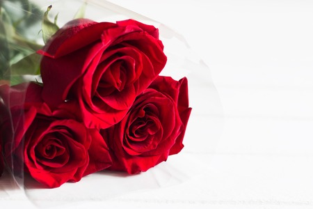 Three red roses bouquet white background copy space.